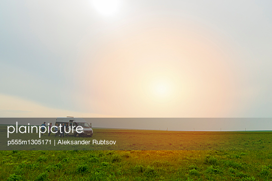 Caucasian friends standing in field near van - p555m1305171 by Aleksander Rubtsov