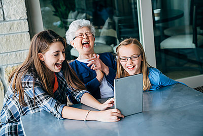 High angle view of happy granddaughters and grandmother using tablet computer on porch - p1166m1489093 by Cavan Images