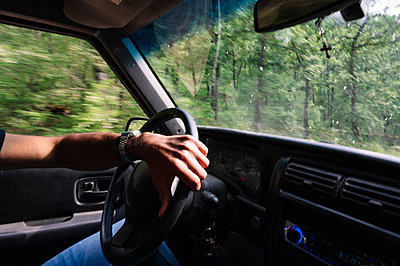Hand of man on steering wheel driving during road trip - p300m2202718 by Jose Luis CARRASCOSA