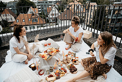 Friends enjoying adundant picnich on rooftop trerrace - p300m2266636 by letizia haessig photography
