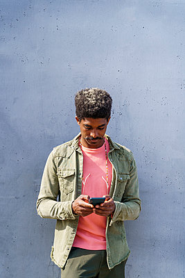 Man using smart phone by wall during sunny day - p300m2281336 by VITTA GALLERY