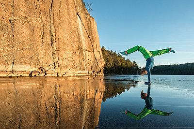 Woman doing yoga on frozen lake - p312m1471044 by Fredrik Schlyter