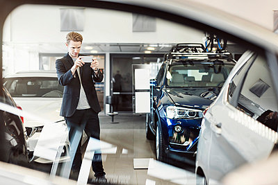 Man photographing car through mobile phone at dealership store - p426m1036563f by Maskot