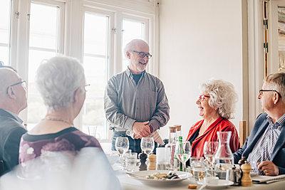Senior friends talking in restaurant - p426m2149131 by Maskot