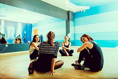 Caucasian dancers sitting on studio floor - p555m1412359 by Aleksander Rubtsov