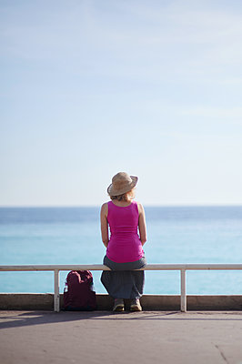 Woman with straw hat looks out onto the sea, Côte d'Azur, Nicea, France - p556m2185350 by Wehner