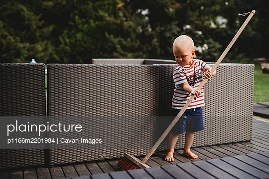 Young male child barefoot sweeping backyard patio with big broom - p1166m2201984 by Cavan Images