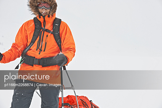 Woman dragging expedition sled in winter landscape - p1166m2268874 by Cavan Images