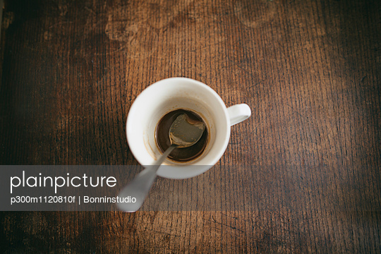 Cup with spoon and remains of coffee on wood - p300m1120810f by Bonninstudio