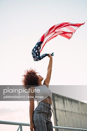 Young woman swinging American flag - p300m2042212 von Kike Arnaiz