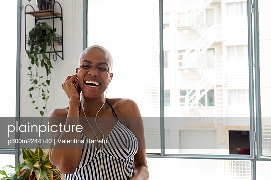 Happy woman standing at home using smartphone and headphones - p300m2244140 by Valentina Barreto