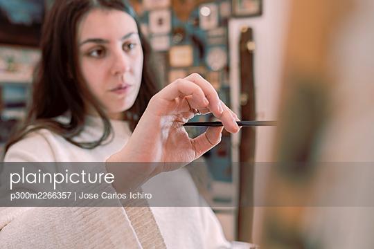 Young female artist painting at studio - p300m2266357 by Jose Carlos Ichiro