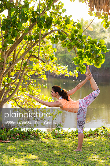 Hispanic woman practicing yoga in park - p555m1409984 by Rick Gomez