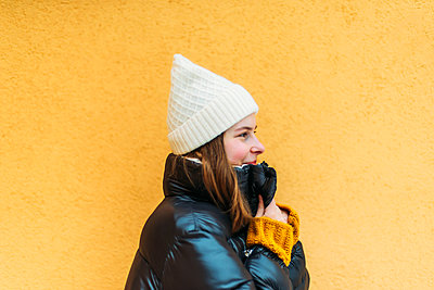 Young woman  while standing against yellow wall - p1166m2153371 by Cavan Images
