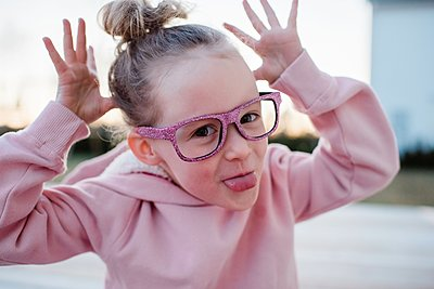 portrait of a young girl pulling silly faces with sparkly glasses on - p1166m2163496 by Cavan Images