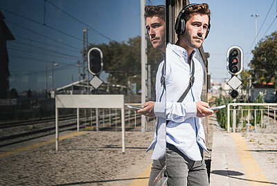 Young man with headphones and smartphone standing in train door - p300m2156717 by Uwe Umstätter