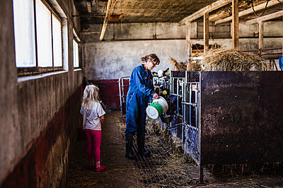 Grandmother with granddaughter in cowshed - p312m2190996 by Anna Johnsson