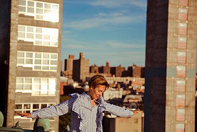 Balancierende junge Frau auf Dach - p432m1185606 von mia takahara