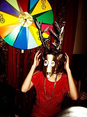 Woman wears deer mask with antlers - p972m1088669 by Björn Terring