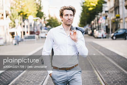 Smiling man walking with hand in pocket and jacket over shoulder in city - p300m2221709 by Uwe Umstätter