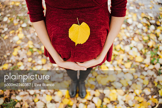 Yellow leaf on pregnant woman's belly in park - p300m2240357 by Eva Blanco