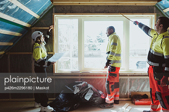 Female building contractor examining window with male construction worker at site - p426m2296180 by Maskot