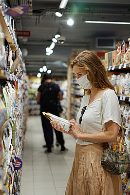 A woman wearing a cloth mask is shopping - p1610m2208784 by myriam tirler