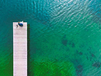 Germany, Bavaria, Chiemsee, man sitting on jetty - p300m1581566 by Michael Malorny