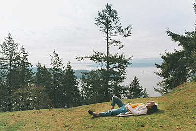 Woman relaxing in nature, lying on grass - p300m2103036 by Crystal Sing