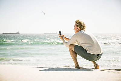 Man taking a smartphone picture on the beach - p300m2167545 by Floco Images