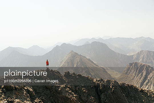 Woman looking at view while standing on peak of mountain against clear sky - p1166m2258396 by Cavan Images