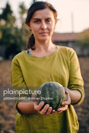 Bulgaria, Razgrad, woman holding small watermelon in garden - p300m2012450 von Borislav Zhuykov