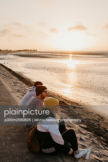 Namibia, Walvis Bay, three friends relaxing at sunset - p300m2080825 by letizia haessig photography