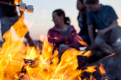 Close-up of campfire against fiends camping at dusk - p1166m1174132 by Cavan Images