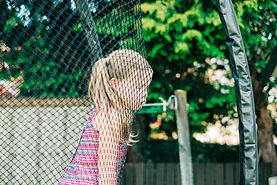 Young girl with grumpy face leaning on trampoline netting - p1166m2208056 by Cavan Images