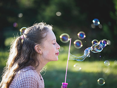 Girl (12-13) blowing bubbles - p1427m1504583 by WalkerPod Images