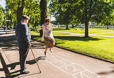 Senior woman playing hopscotch while husband watching her - p300m1460656 by Uwe Umstätter