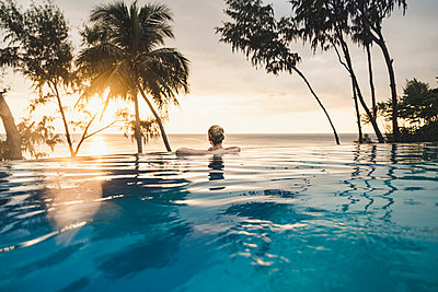 Rear view of woman in infinity pool at sunset, Nai Thon Beach, Phuket, Thailand - p300m2166281 by Christophe Papke