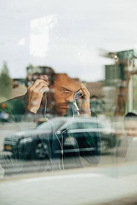 Businessman wearing headphones seen through glass window at office - p426m2159701 by Maskot