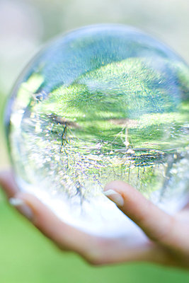 Woman holding glass ball in hand outdoors - p6242324f by Rafal Strzechowski
