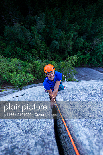 Man smiling and looking up at camera while climbing off width Squamish - p1166m2191920 by Cavan Images