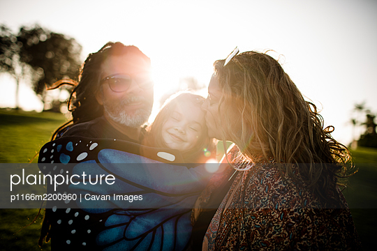 Aunt, uncle and niece hugging and posing during sunset - p1166m2200960 by Cavan Images