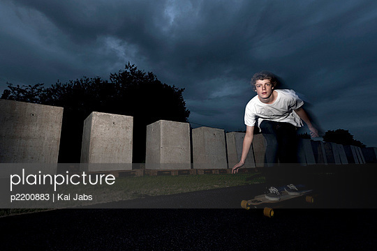 Boy at night on longboard - p2200883 by Kai Jabs