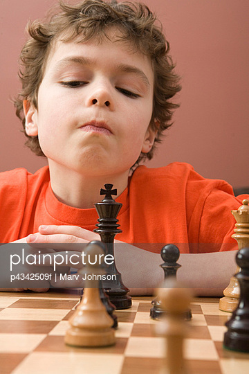 Boy playing chess - p4342509f by Marv Johnson