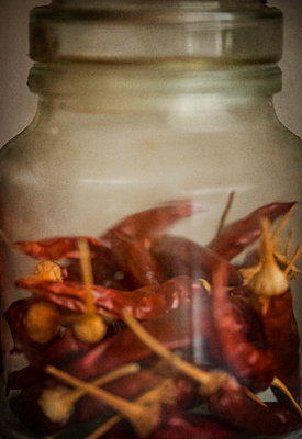 Close-up of a jar of dried red chillies - p1047m1007721 by Sally Mundy