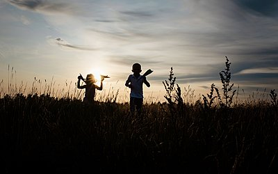 silhouette of brother and sister playing in a meadow at sunset - p1166m2137848 by Cavan Images
