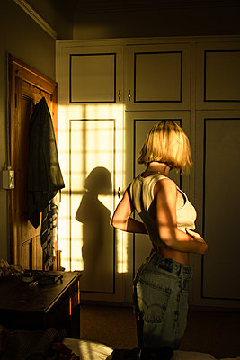 Young woman in dressing room in the sunlight - p1640m2279070 by Holly & John