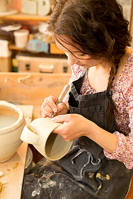 Potter in workshop working on earthenware jug - p300m1023322f by Roman Märzinger