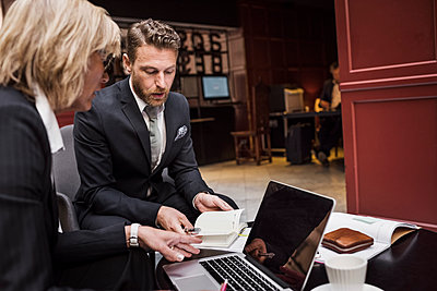 Business people discussing contract in hotel reception - p426m1442734 by Maskot