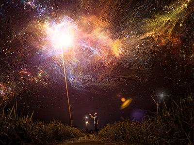 Caucasian man reaching towards light in starry night sky - p555m1311967 by Kirk Marsh
